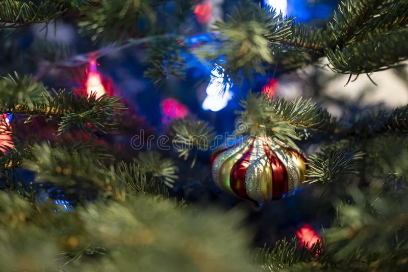 Beautiful multi-colored glass toy on a Christmas tree with a garland. Beautiful multi-colored glass toy on a Christmas tree with a garland, on a blurred stock image