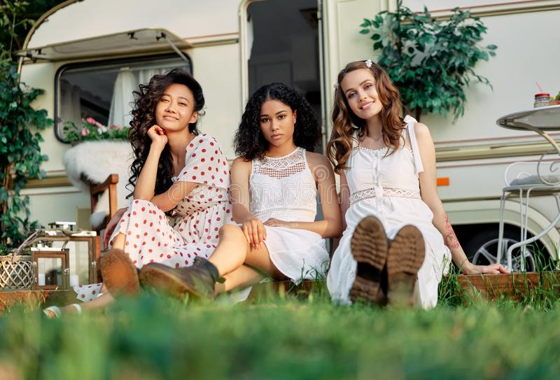 Beautiful multi ethnic girls posing near camper van outdoors stock photo