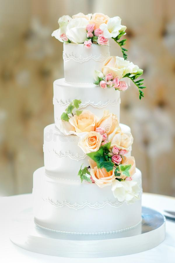 Beautiful multi-tiered wedding cake decorated with fresh flowers royalty free stock photography