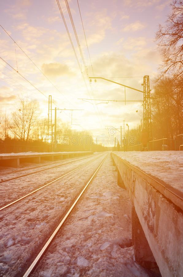 Beautiful multicolored cloudy sky during a bright orange sunset. Track passes through the village plantations. Russian railway la. Ndscape in winter stock images