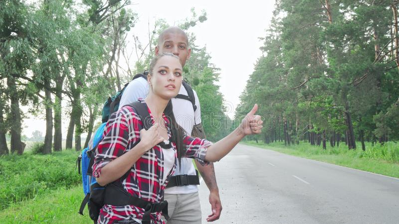Beautiful multiracial couple hitchhiking on countryside road. Lovely couple with backpacks enjoying travelling together, catching a ride on a road. Travel royalty free stock images