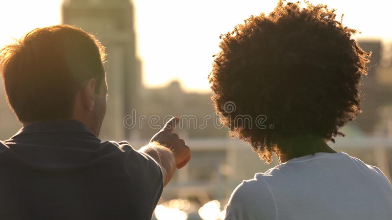 Beautiful multiracial couple looking at city from the roof at sunny day, date royalty free stock image