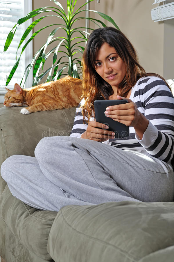 Beautiful multiracial woman reading with cat