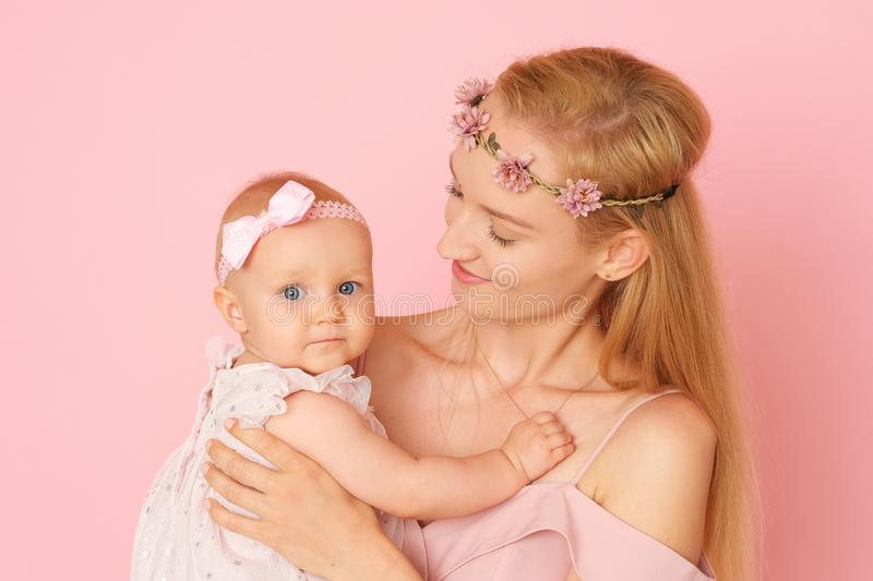 Beautiful portrait of young mom and her little, cute daughter. The picture full of love. Beautiful mum and her little daughter in ceremonial pink dresses stock photo
