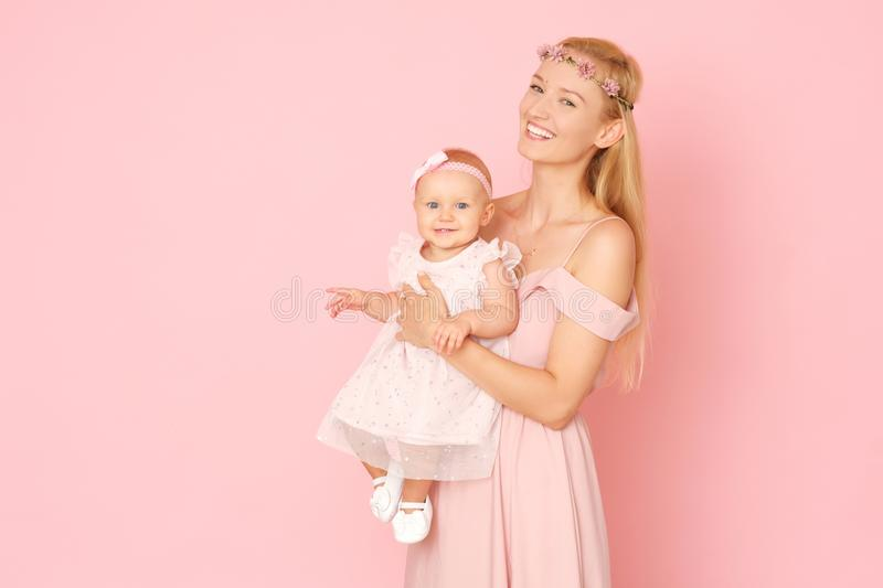 Beautiful portrait of young mom and her little, cute daughter. The picture full of love. Beautiful mum and her little daughter in ceremonial pink dresses royalty free stock images