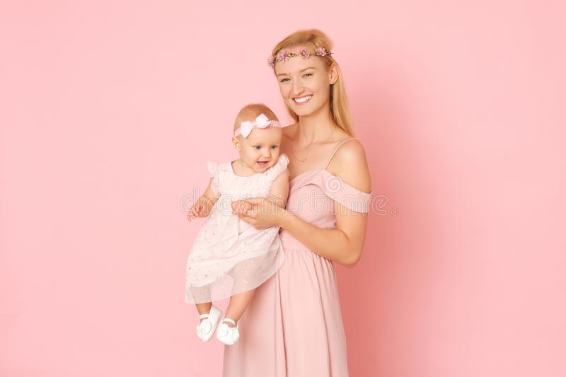 Beautiful portrait of young mom and her little, cute daughter. The picture full of love. Beautiful mum and her little daughter in ceremonial pink dresses royalty free stock image