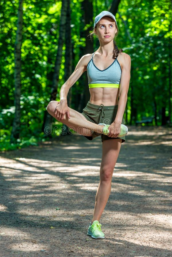 Beautiful muscular athletic girl warms up her muscles before jogging stock photography