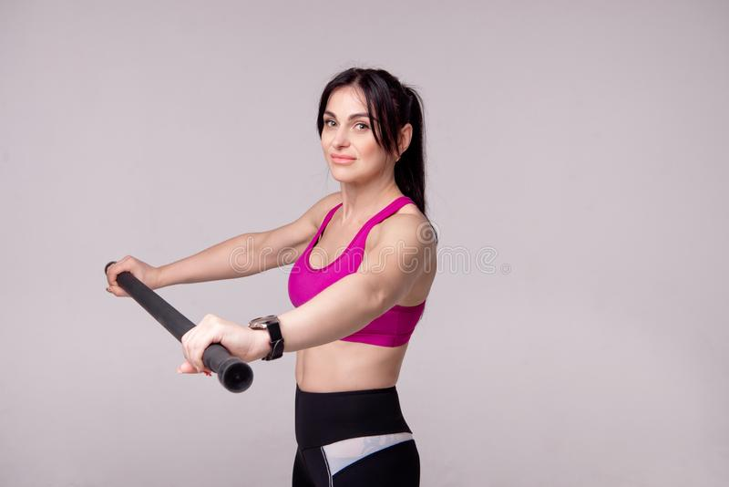Beautiful muscular woman doing exercise with gymnastic stick on a gray background. Beautiful muscular woman doing exercise with gymnastic stick on a gray royalty free stock photo