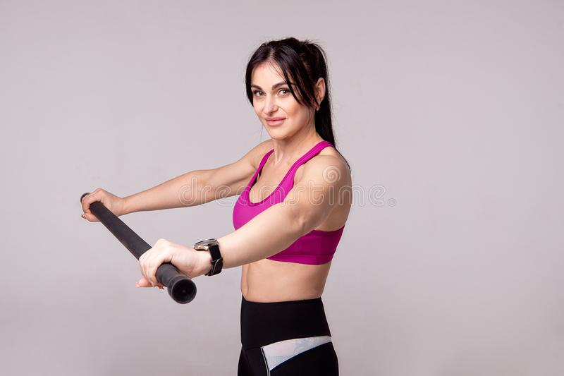 Beautiful muscular woman doing exercise with gymnastic stick on a gray background. Beautiful muscular woman doing exercise with gymnastic stick on a gray stock images