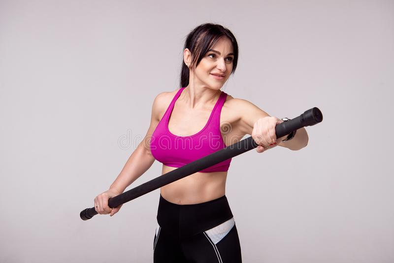 Beautiful muscular woman doing exercise with gymnastic stick on a gray background. Beautiful muscular woman doing exercise with gymnastic stick on a gray royalty free stock images