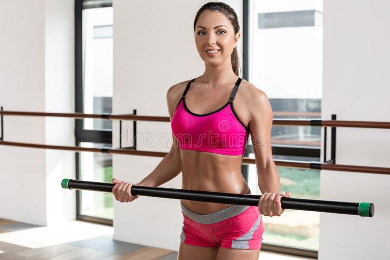 Beautiful muscular woman doing exercise with gymnastic stick at the gym. stock images
