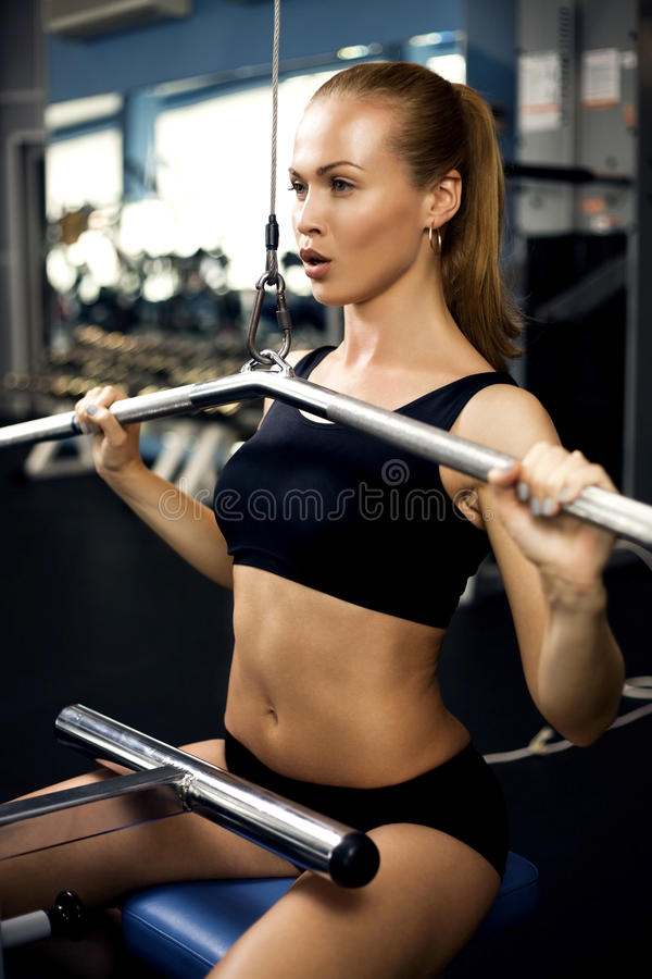 Beautiful muscular woman exercising building muscles. Beautiful muscular fit woman exercising building muscles royalty free stock image
