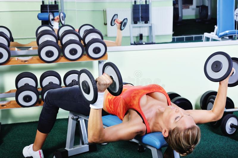 Beautiful muscular woman exercising in gym. Beautiful muscular woman exercising in a gym stock photo