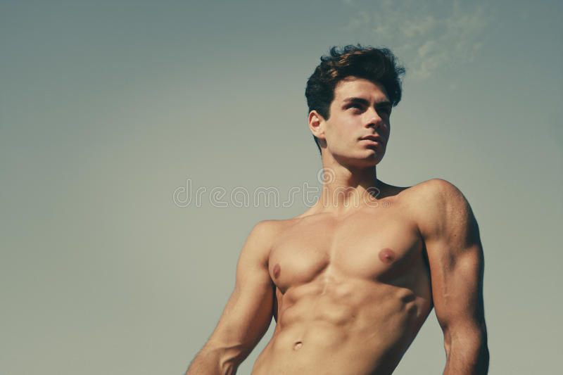 Beautiful and muscular young man shirtless. A beautiful young Italian man posing at the sea, athletic and muscular body royalty free stock images