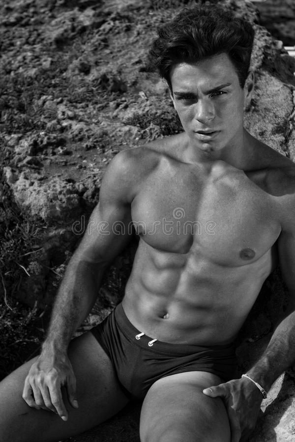 Beautiful and muscular young man shirtless. A beautiful young Italian man posing at the sea shirtless / serious and scrutinizing attitude / athletic and muscular stock images