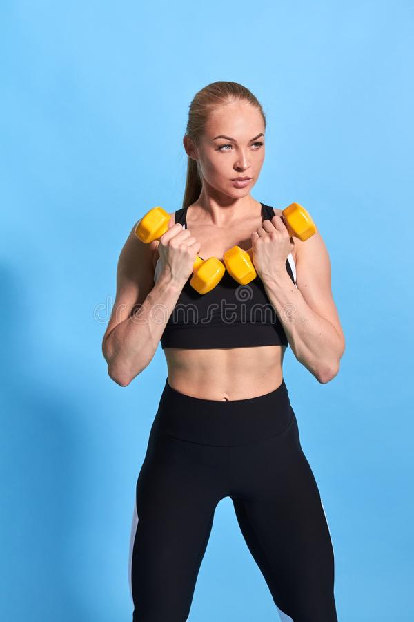 Beautiful muscular young woman in stylish sportswaer lifting weights royalty free stock images