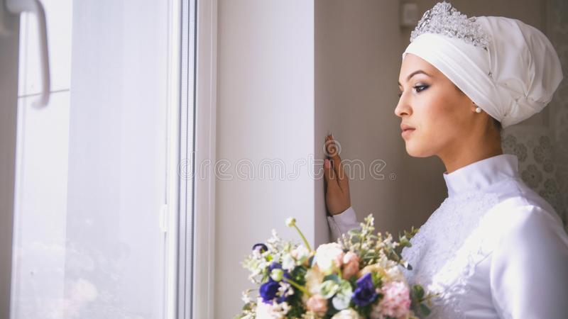Beautiful muslim bride looking out the window holding the bouquet of flowers royalty free stock photos