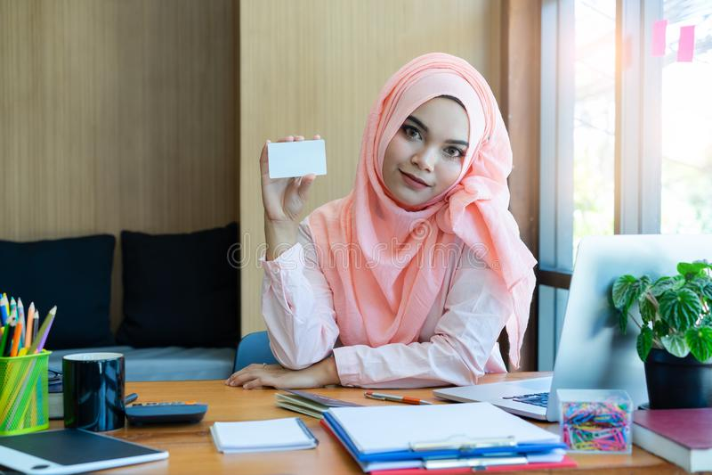 Beautiful Muslim business woman hand holding blank credit card in modern office. royalty free stock photos