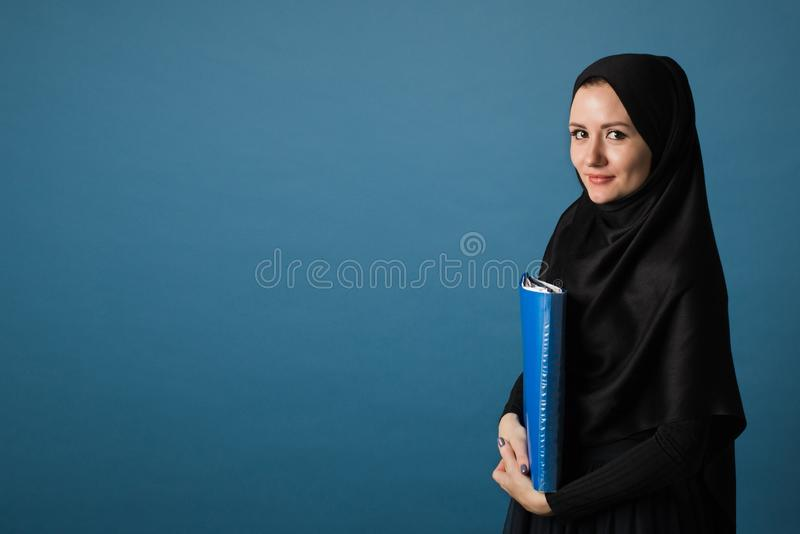 Muslim girl secretary or office manager in hijab stands with a folder of papers in her hands on a blue background in the royalty free stock photo