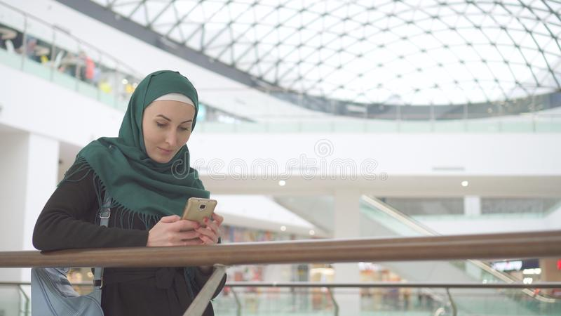 Beautiful muslim girl in hijab uses smartphone in modern business center royalty free stock images