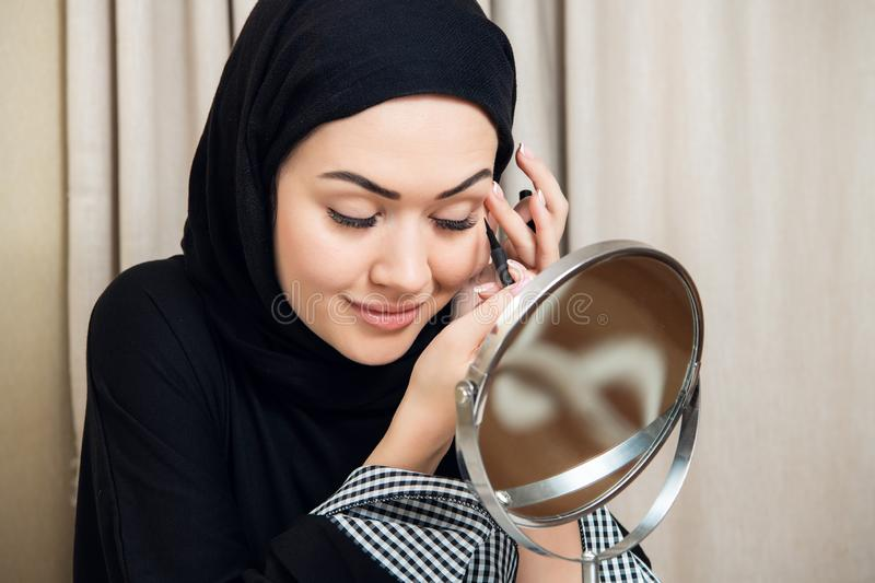 Beautiful muslim woman applying eyeshadow eyeliner at home stock photos