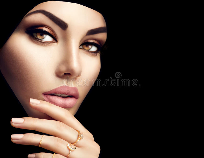 Beautiful muslim woman face portrait. Beauty arabian woman with perfect makeup and manicure isolated on black background royalty free stock photo