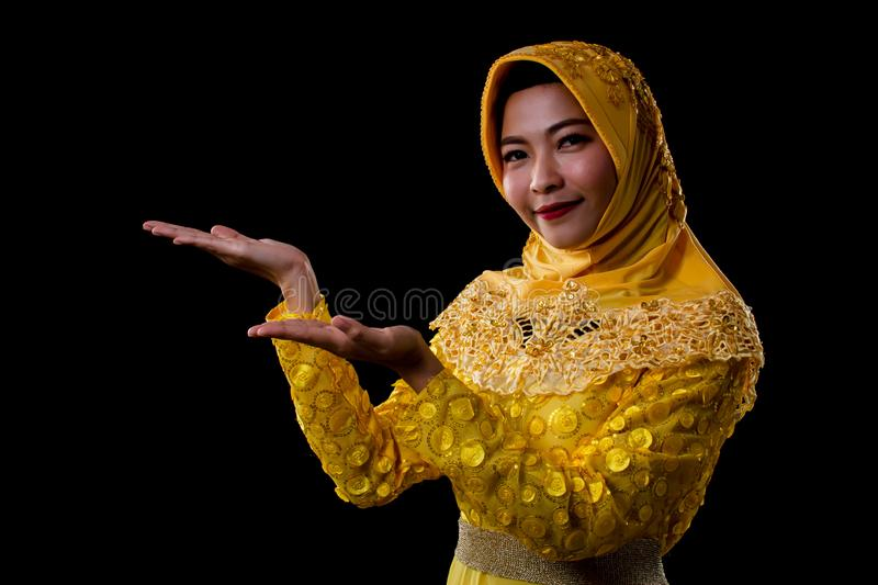 A beautiful muslim woman making her gestures for showing something with copy space royalty free stock photography