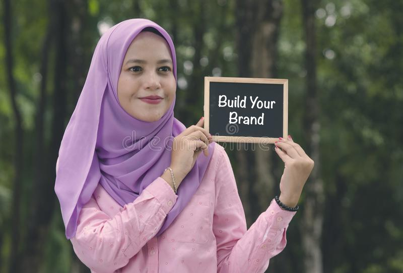 Beautiful muslimah stand and holding chalkboard with word BUILD YOUR BRAND. stock images