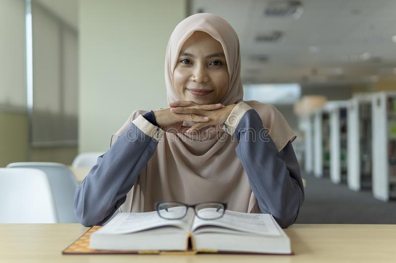 Beautiful young student in the library. A beautiful Muslimah student sitting in the library and smiling stock photo
