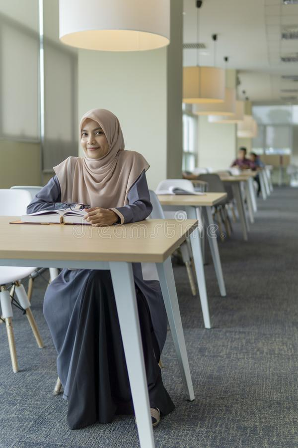 Beautiful young student in the library. A beautiful Muslimah student sitting in the library and smiling royalty free stock image