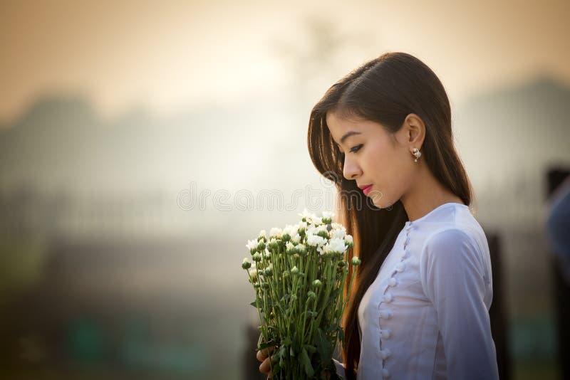 Beautiful Myanmar woman and white the flower on U Bein Bridge Ma royalty free stock image