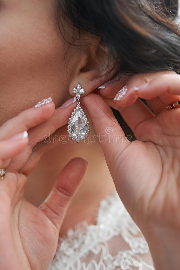 Beautiful, mysterious bride puts earrings. wonderful Wedding accessories. Soft selective focus. happy day stock photos