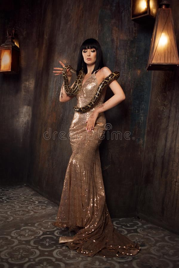 Beautiful and mysterious brunette in a gold dress and with a snake. Beautiful brunette in a gold dress and with a snake stock photo