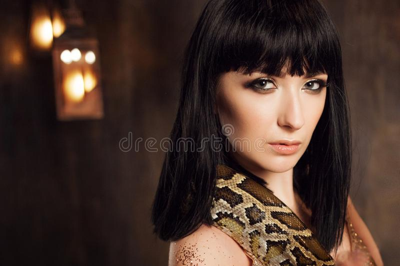 Beautiful and mysterious brunette in a gold dress and with a snake. Beautiful brunette in a gold dress and with a snake. Close-up stock image