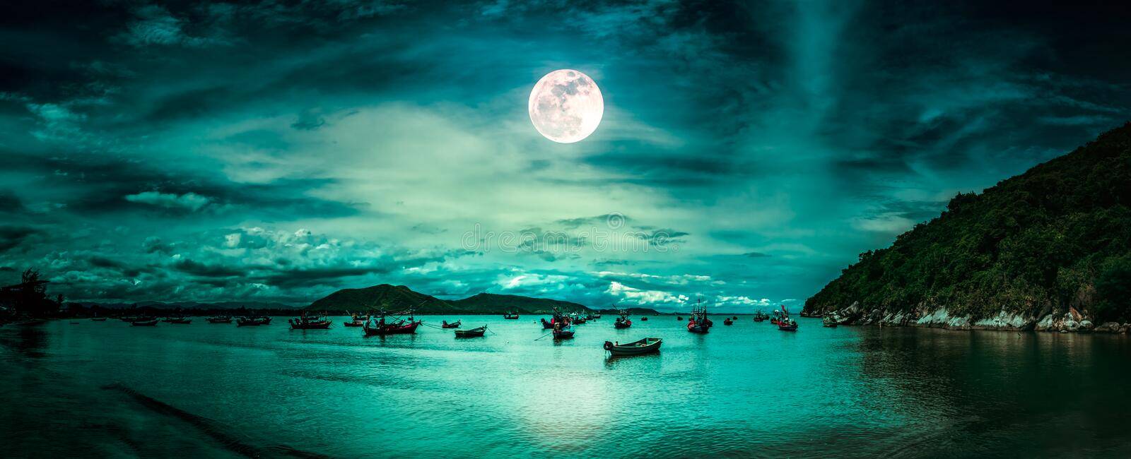 Beautiful mysterious nature landscape. Beach by the sea with mountains and full moon at nighttime stock photos