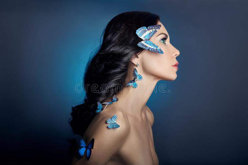 Beautiful mysterious woman with butterflies blue color on her face, brunette and paper artificial blue butterflies on the girls royalty free stock photography