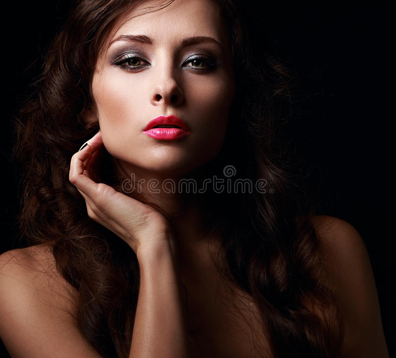Beautiful mystery woman face kissing her hot pink lips. On black background. Closeup royalty free stock photography