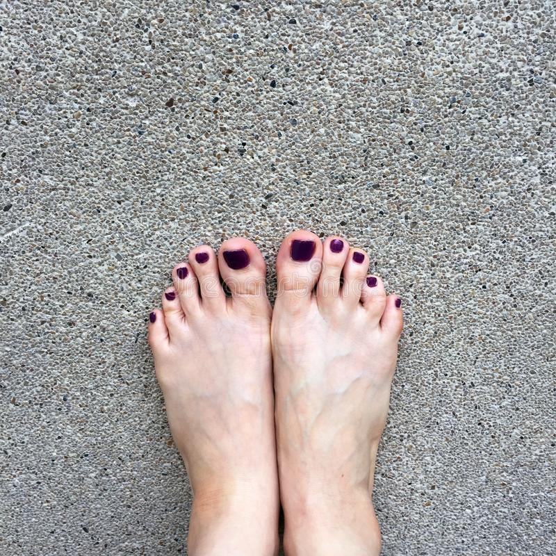 Beautiful Nail, Close Up Woman`s Bare Feet and Red Nail Polish on Cement Floor Background stock image