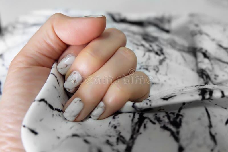 Beautiful Nail Polish, Manicure Nail. Close Up Granite Gray Nails on the Granite Stone Fabric royalty free stock photo