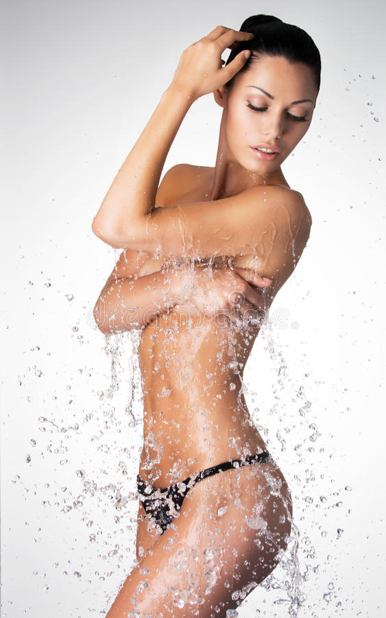 Beautiful naked woman with wet body and splashes of water royalty free stock photography