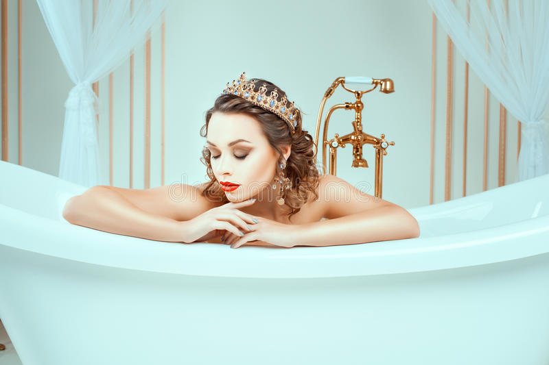 Beautiful naked young woman sitting in expensive jewelry bath. In the face of a bright fashion make-up on her head a crown stock images
