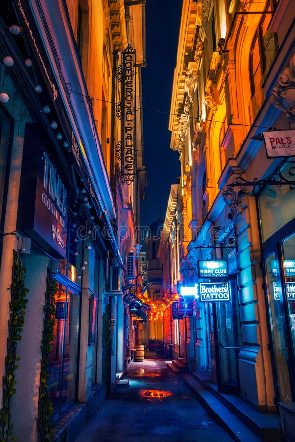 Beautiful narrow alley with night clubs and cocktail bars shot i. N the night downtown in Bucharest city royalty free stock images