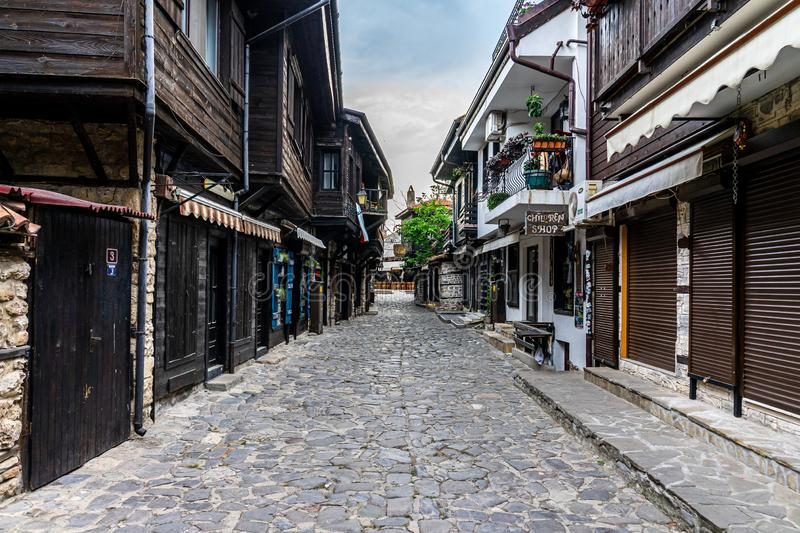 Beautiful and narrow street with restaurants, cafes and shops of the ancient seaside town. royalty free stock images