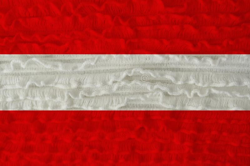 Beautiful national flag of the country of austria on a soft background texture of knitted wool with small flounces of linen royalty free stock photography