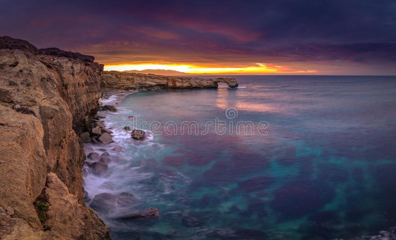 Beautiful natural big rock arch at sunset near Rethimno, Crete. royalty free stock images