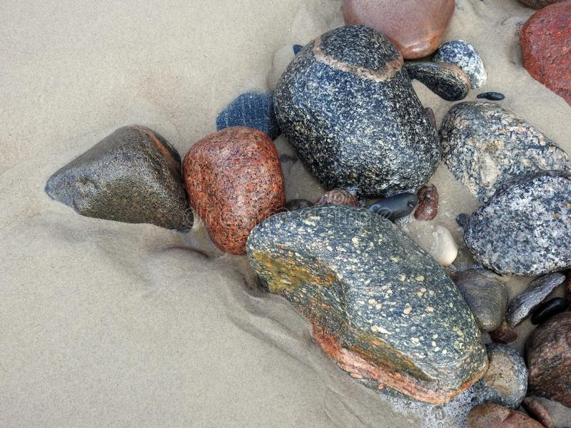 Colorful natural stones on sand near sea, Lithuania royalty free stock photography