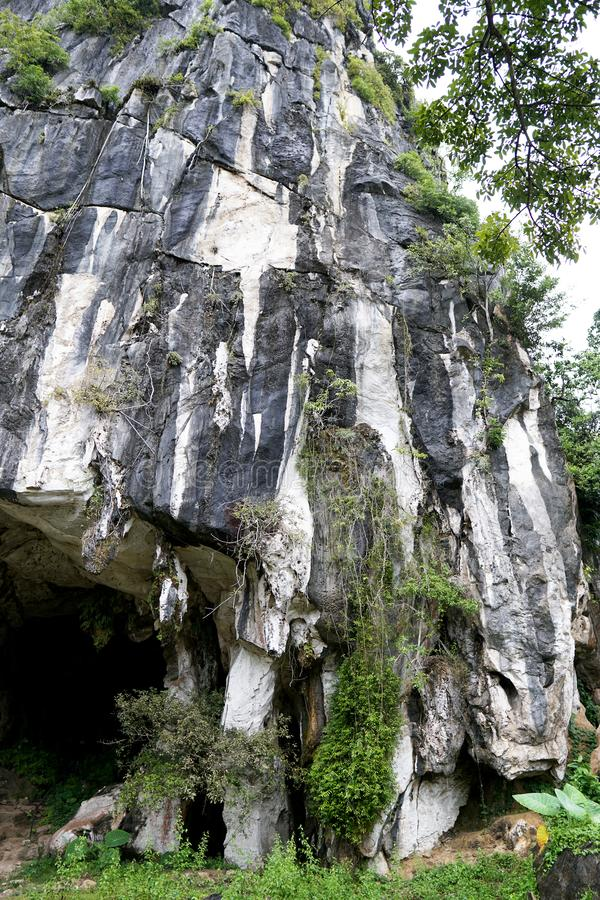 Beautiful natural limestone cave entrance in Malaysia. Limestone Hill and Cave.Jungle covered and dramatic rounded hill and huge h royalty free stock photography