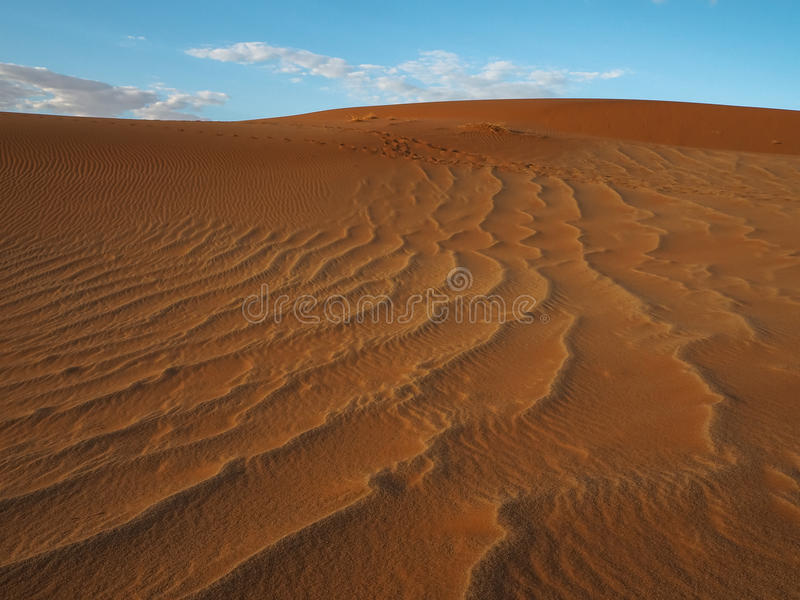 Beautiful natural pattern of rusty red sand dune with blue sky and white cloud background, Sossus, Namib Dessert royalty free stock photo