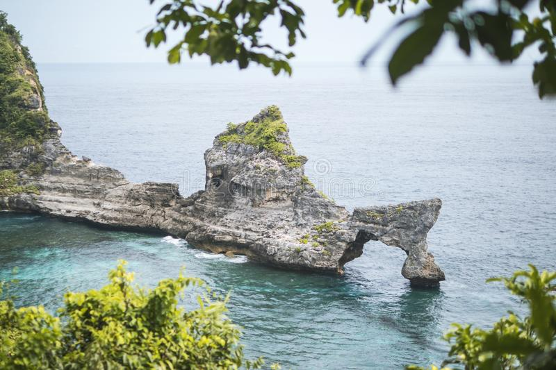 Beautiful Natural Rock Arch Island in the Sea at Atuh Beach in Nusa Penida, Bali, Indonesia. Aerial View. stock photo