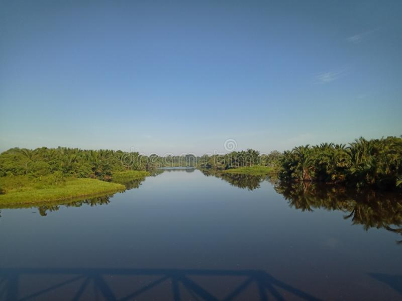Beautiful natural scenery of river in southeast Asia tropical green forest with sky in the morning, photo from the bridge stock photo